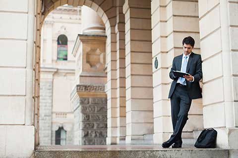 Businessman using a tablet against an archway